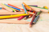 Coloured pencils scattered on a table. crayons — Stock fotografie