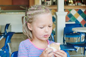 Little girl eating ice cream in a cafe — Stock Photo