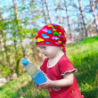 Little beautiful girl in bright clothes holding a bottle in hand — Foto de Stock