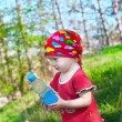Little beautiful girl in bright clothes holding a bottle in hand — ストック写真