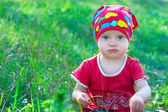 Serious little girl in red clothes sitting in the middle grass — Stock Photo