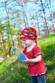 Petite fille belle en vêtements lumineux, tenant une bouteille dans la main — Photo