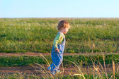 Jolly child in the jeans coverall off down the road — Stock Photo