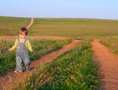 Sweet child in the jeans coverall go to the dirt road — Stock Photo