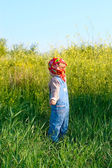 Nice child in the jeans coverall and red bandana pluck flowers — Stock Photo