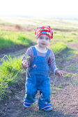 Pretty child in the red headscarf and jeans overall — Stock Photo