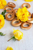 Roll and yellow roses on the light board — Stock Photo
