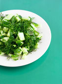 Cucumber salad on the round white plate on the green paper — Stock Photo