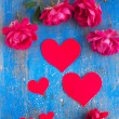 Stock Photo: Big and small hearts and many red rose on blue