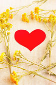 Red heart in the frame of wild flowers — Stock Photo
