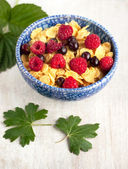 Corn flakes with raspberrys and currants — Stock Photo