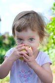 Small girl bite off juicy apple — Stock Photo