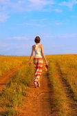 Slender woman to walk on the earth road — Stock Photo