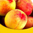 Rich peach in the yellow plate — Stock Photo