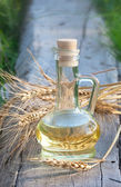 Ears of wheat and oil in the bottle — Stock Photo
