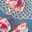 Stock Photo: Sweet pomegranate on lacy placemat