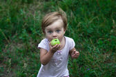 Funny little girl with apple — Stock Photo