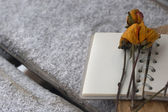 Dry yellow rose on the notebook — Stock Photo