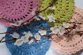 Colorful crocheted napkins and flowering branches — Stock Photo