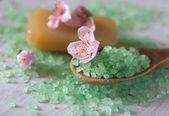 Salt bath on a wooden spoon, soap and flowers — Stockfoto