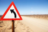 Road sign indicating left turn in road — Stock Photo
