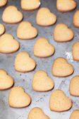 Home made heart shaped cookies on baking tray — Stock Photo