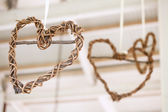 Wooden weaved hearts hanging off roof trusses at wedding, selective focus — Stock Photo