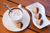 Chocolate dipped heart shaped shortbread cookies and a cup of ca — Stock Photo