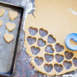 Plastic heart shaped cookie cutter and raw dough cookies on meta — Stock Photo