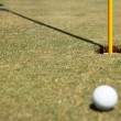 Golf ball and flag in hole — Stock Photo