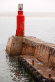Bright red lighthouse on pier in harbor — Stock Photo