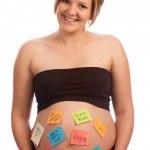 glückliche schwangere Frau mit Haftnotizen auf Bauch — Stockfoto