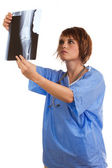 Young female doctor examining x-ray image of human knee — Stock Photo