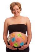 Attractive pregnant female with self-adhesive notes on stomach — Stock Photo