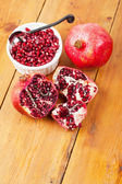 Pomegranate pips in a bowl with whole fruit on wooden surface — Stock Photo