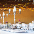 Wedding reception hall with decor including candles and cutlery — Stock Photo #35823915