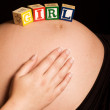 Caucasian pregnant woman with wooden blocks on tummy — Stock Photo #39000551