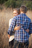 Young adult couple hugging in tall grass outside — Stock Photo