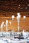 Candelabra with candles on decorated wedding reception tables — Stock Photo