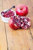 Fresh pomegranate fruit and pips in white bowl — Stock Photo