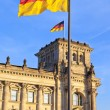 Reichstag with flags in the german capital Berlin - Stock Photo