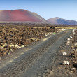 Lava Fields and a road leading to the mountains of fire, Timanfaya National Park in Lanzarote Island — Stock Photo