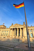 Reichstag with German flags in late afternoon light, Berlin — Stock Photo