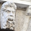 Limestone sculpture of a head on a Pordenone palace, Italy - Stock Photo