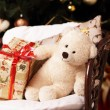Stock Photo: Gifts under by fir-tree at head with bruin