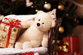 Festive soft bruin with gifts under the New-year tree — Stock Photo