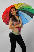 The dark girl under a beach umbrella — Stock Photo
