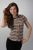 Girl with lush hair in a checkered shirt on — ストック写真