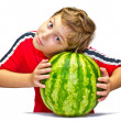 Little boy examines the maturity of watermelon squeezing his hands — Stok fotoğraf