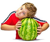 Little boy examines the maturity of watermelon squeezing his hands — Stock Photo